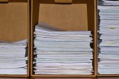 Three stacks of office paperwork filed into different cardboard compartments, ascending from left to right.