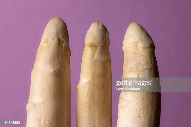 Three stalks of white asparagus suggestive of three penises