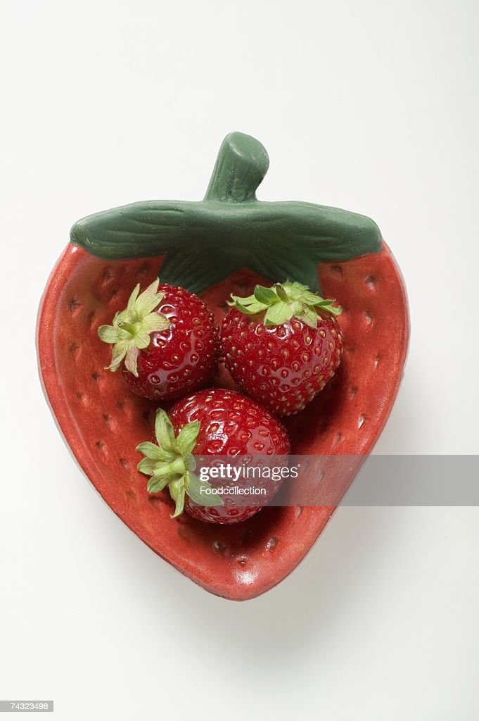 Three strawberries in red strawberry-shaped dish : Stock Photo