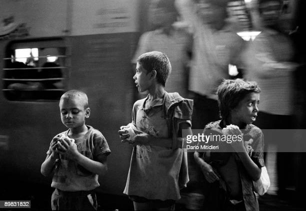 Three street children waiting for the train to take them from Borivili station to the Victoria Terminus station in Bombay India
