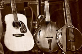 A medium closeup of three stringed folk instruments on a stage - a guitar (6-string), a bass mandolin (bouzouki), and a Banjo (5-string). The image is a brown monochrome. An amp and other audio equipm