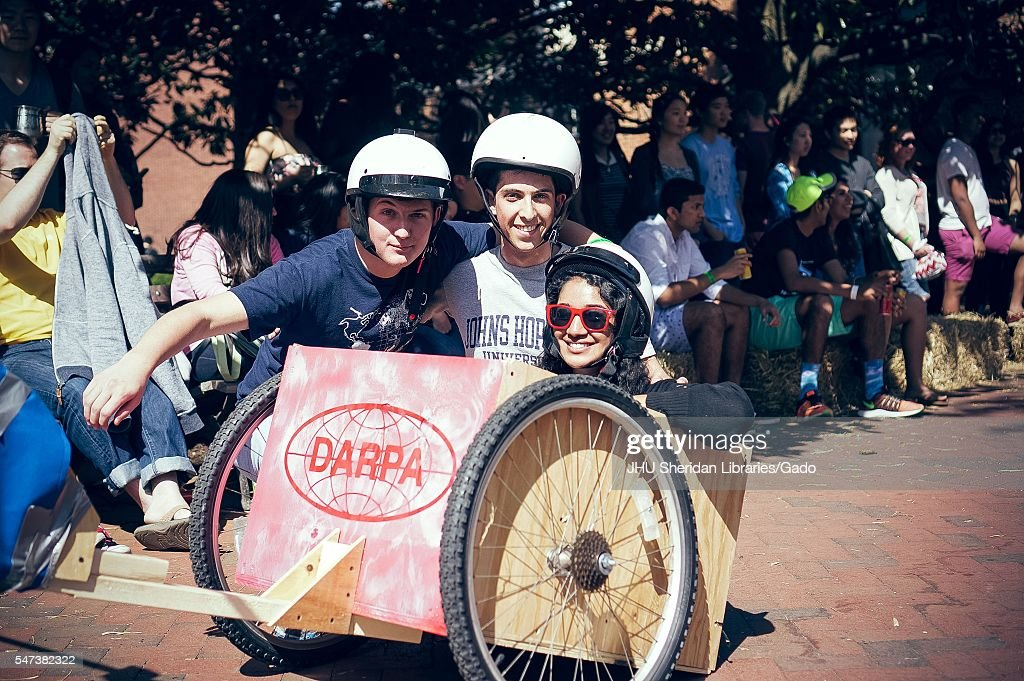 Three students wearing helmets pose for a photo from inside a wooden cart with wheels as onlookers watch from the side in the shade during a carnival...