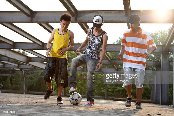 Three stylish young men kick a soccer ball in an abandoned industrial area.