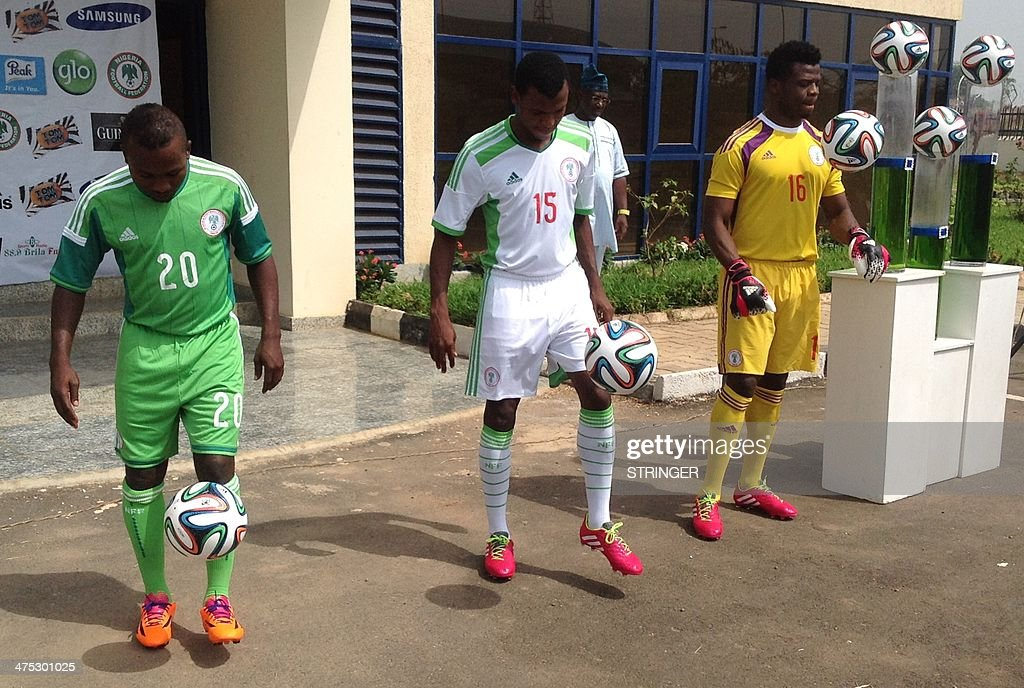 Three Super Eagles, name of the Nigerian national football team, midfielder Abdullahi Shehu (C), striker Ejike Uzuoenyi (L) and keeper Chigozie Agbim (R) juggle with balls as they pose with Nigeria's new official jersey for the 2014 World Cup in Brazil in Abuja on February 27, 2014. The Nigeria Football Federation has presented the new jersey that the national football team, the Super Eagles will wear specially for the FIFA World Cup Brazil 2014. Nigeria will make their fifth appearance at the World Cup in Brazil. They are drawn against Argentina, Iran and Bosnia-Hersegovina in the first round of the tournament, which kicks off on June 12. AFP PHOTO / STRINGER