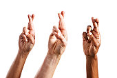 Three superstitious hands with fingers crossed, isolated on white