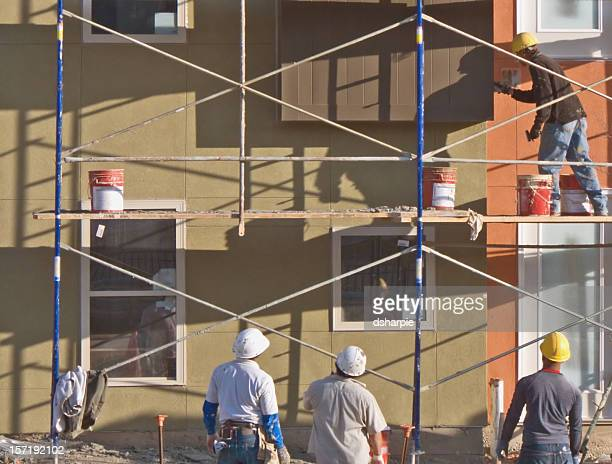 Three supervisors watch a scaffolding worker