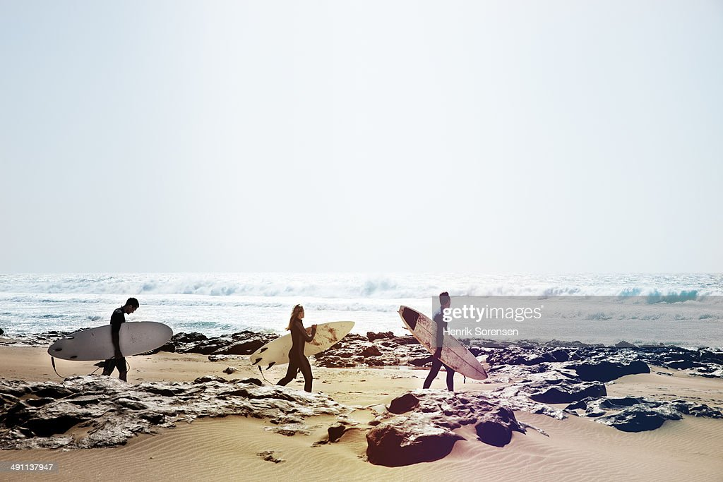 Three surfers on the beach : Stock Photo