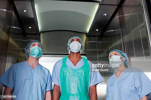 Three surgeons in hospital elevator