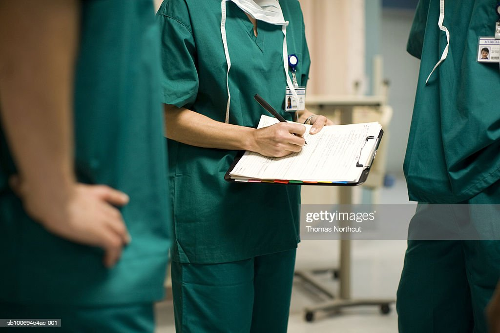 Three surgeons in operating room, mid section : Stock Photo