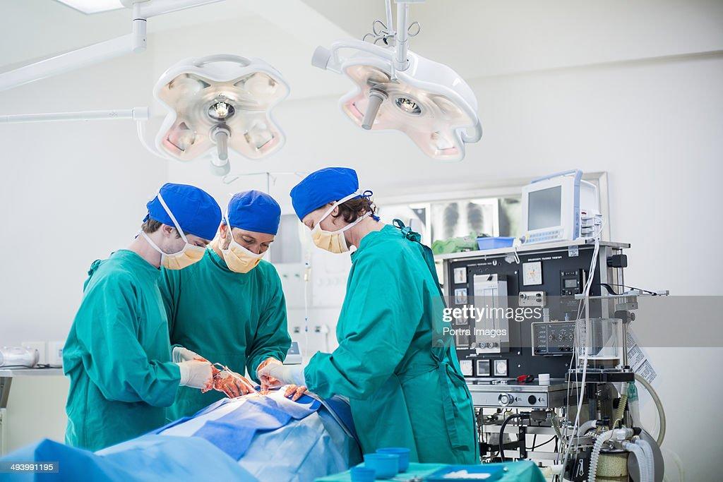 Three surgeons performing a surgery