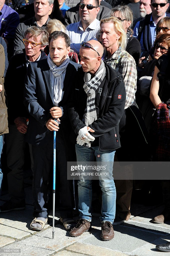 Three survivors (the two foreground) and US Glen Plake (second ground, C) take part in a memorial ceremony to pay tribute to the victims of the last week avalanche on Nepal's Manaslu mountain, on October 2, 2012, in Chamonix, that is considered the birthplace of European alpinism and the home of most of the French climbers killed. The four French -- two guides and two clients -- were among eight people killed after an avalanche swept through their camp on the side of the 8,156-metre (26,759-foot) Himalayan mountain, just hours before the alpinists were to make an attempt to reach the peak's summit. AFP PHOTO / JEAN-PIERRE CLATOT