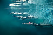 On the image there are 3 female swimmers. They are wearing black one-piece swimwears, cups and swimming goggles. The position of swimmers is straight, they have hands joined in front. Girls are lookin