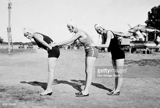Three swimming suited women pose ca 1919