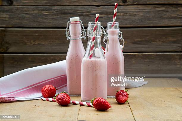 Three swing top bottles of strawberry smoothie