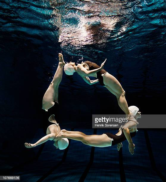 Three synchronised swimmers in formation