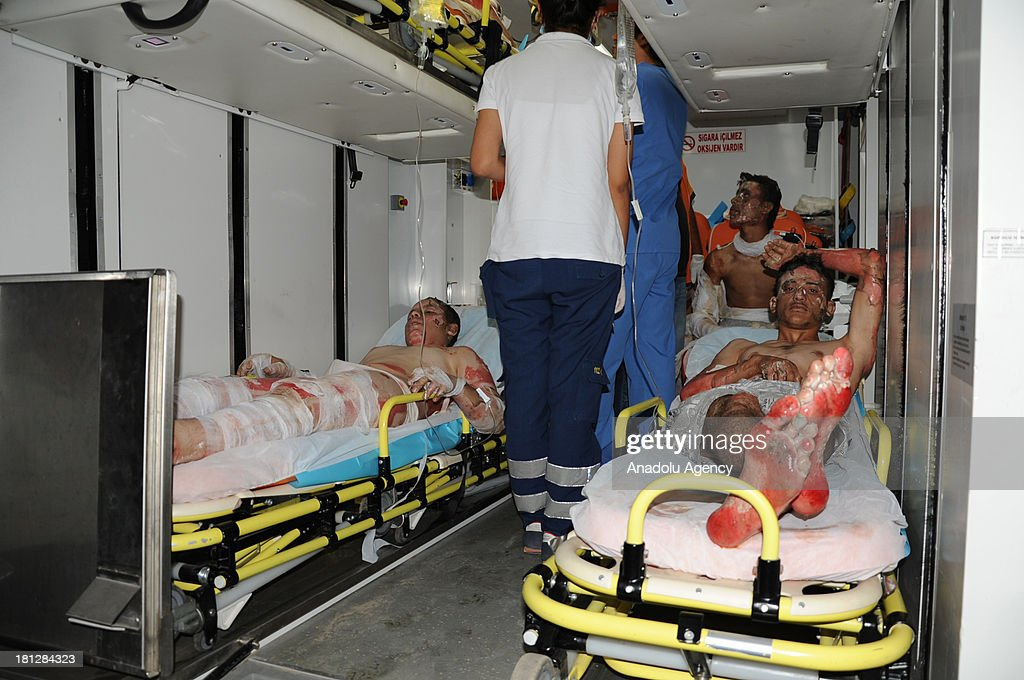 Three Syrian wounded men are carried to the hospital inside an ambulance on August 27,2013 in Hatay, Turkey. Twenty-five Syrians were reported wounded in an air strike on a building which was turned into a school in Terip town of Idlib, Syria on 27 August. Those who are wounded were taken to Turkey's southern city of Hatay which stands ten kilometers away from the border.