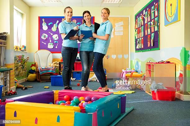 Tre professori in un vivaio Stand sorridente classe