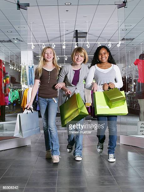 Three teen girls walking out of store