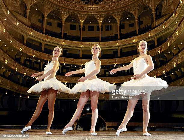 Three teenage ballet dancers on stage