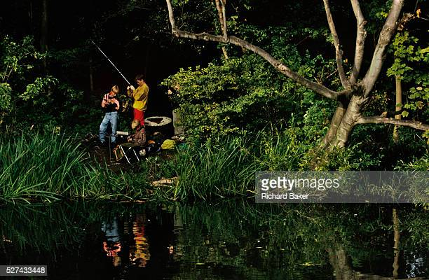Three teenage boys bait their lines in the calm of the River Wandle one of London's lost rivers that still meanders through innercity London on its...