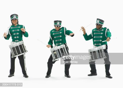 Three teenage boys (14-17) in marching band uniforms playing drums