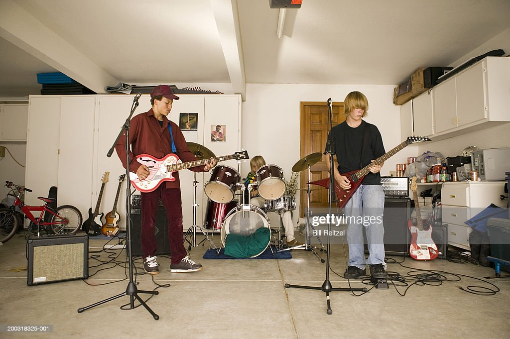 Three teenage boys (13-15) playing bass, guitar and drums in garage