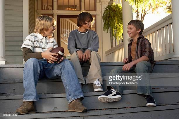 Three teenage boys (13-14) sitting on house steps, holding american football,