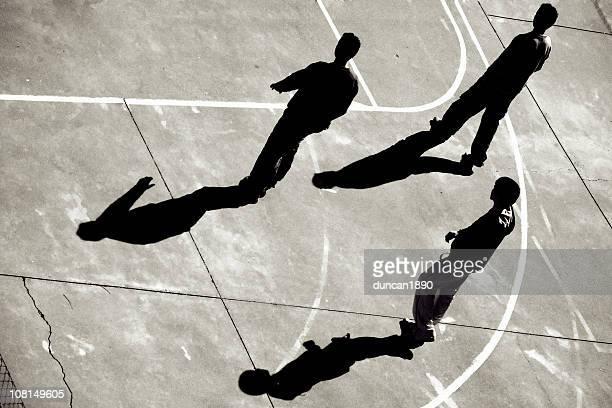 Trois jeunes garçons traversant un terrain de basket-ball