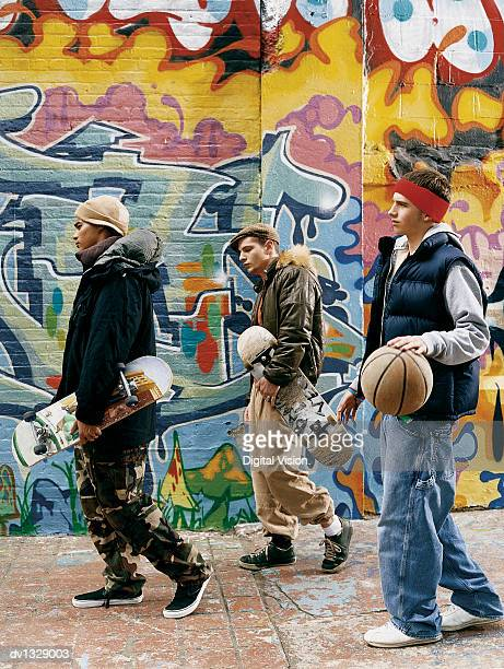 Three Teenage Boys Walking in an Urban Setting with Skateboards, a Basketball and Attitude