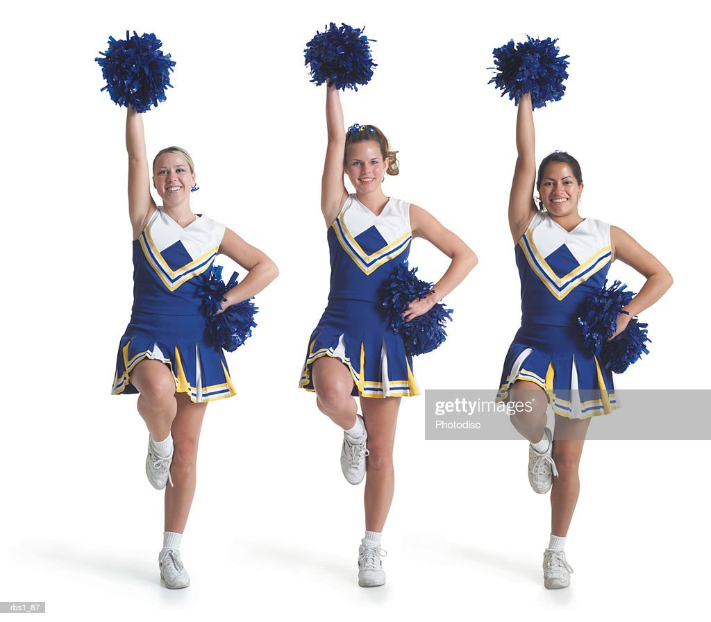 three teenage caucasian female cheerleaders in blue uniforms do a routine and raise their pom poms in the air : Stock Photo