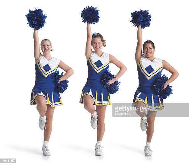 three teenage caucasian female cheerleaders in blue uniforms do a routine and raise their pom poms in the air