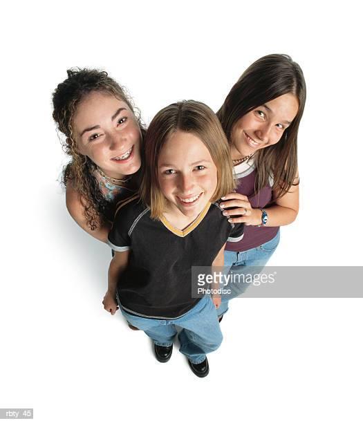 three teenage caucasian girls smile up at the camera playfully