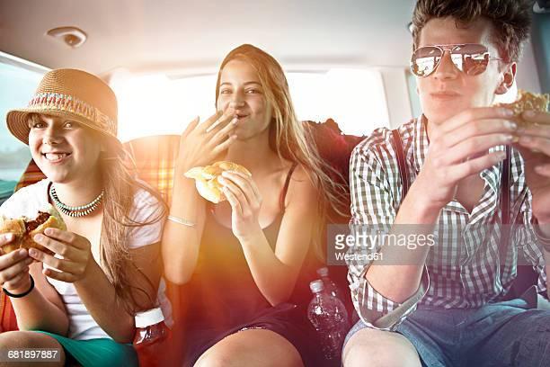 Three teenage friends having a snack in car