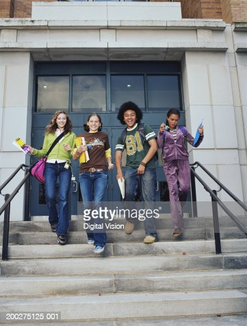 Three teenage girls and teenage boy (13-16) walking down school steps, smiling : Foto de stock