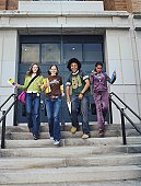 Three teenage girls and teenage boy (13-16) walking down school steps, smiling