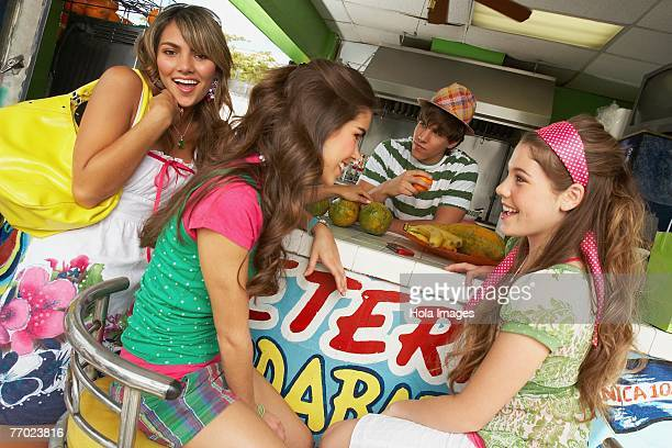 Three teenage girls at a bar counter with a bartender behind them in a juice bar