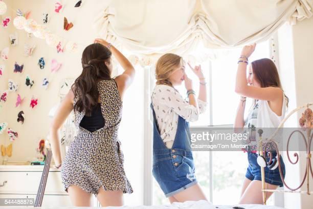 Three teenage girls dancing on bed in bedroom