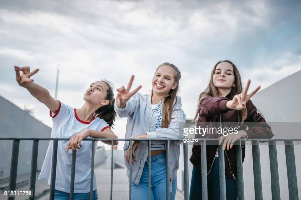 three teenage girls fooling around outdoors