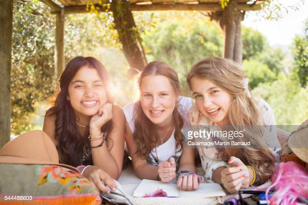 Three teenage girls having fun in tree house in summer