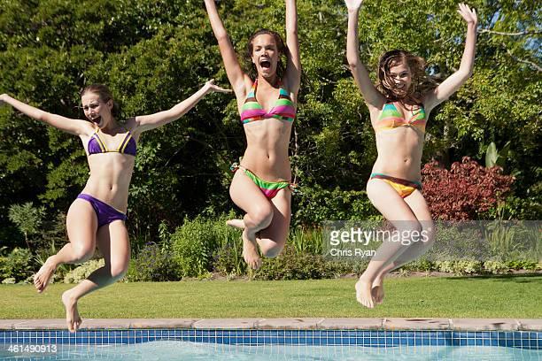 Three teenage girls in bikinis in outdoor pool