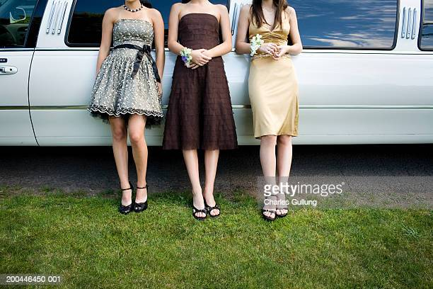Three teenage girls (14-18) in formal dresses beside limo, low section