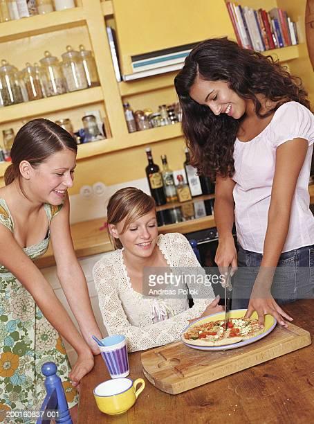Three teenage girls (13-15) in kitchen, one cutting pizza