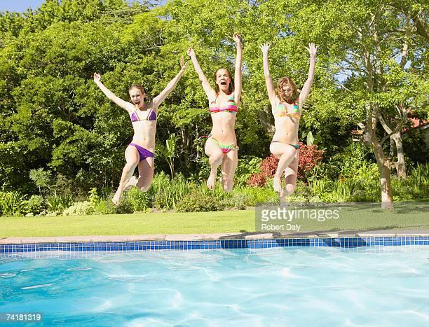 Three teenage girls jumping into pool
