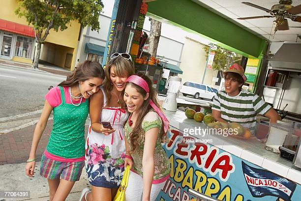 Three teenage girls looking at a mobile phone with a bartender behind them in a juice bar