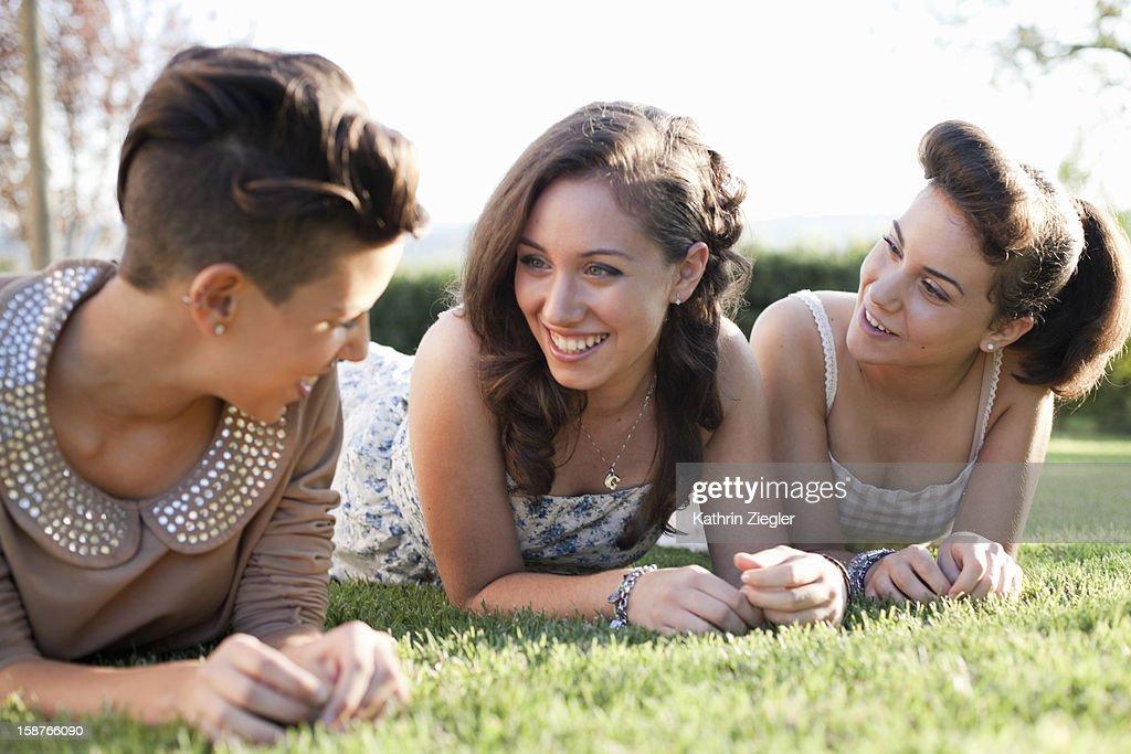 three teenage girls lying on the grass, giggling : Stock Photo