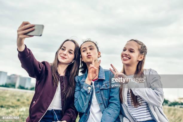 three teenage girls posing for selfie outdoors