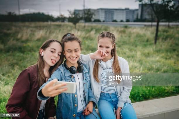 three teenage girls posing for selfie