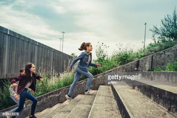 three teenage girls running up stairs