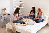 Three teenage girls sitting on bed with laptop talking