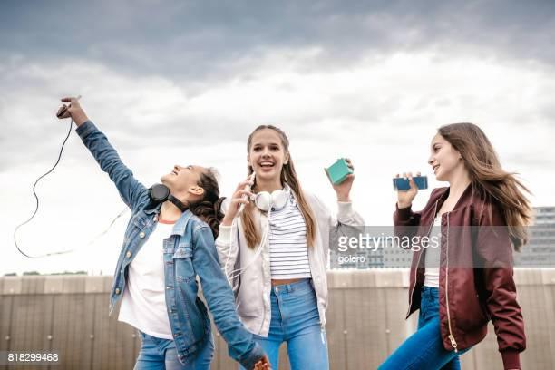 three teenage girls taking cheering outdoors
